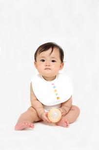 屋内白バックでお座りする新生児の赤ちゃん。新生児、赤ちゃん、育児、健康、愛、幸せイメージの写真素材 [FYI01227940]