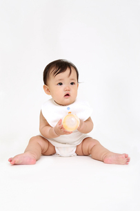 屋内白バックでお座りする新生児の赤ちゃん。新生児、赤ちゃん、育児、健康、愛、幸せイメージの写真素材 [FYI01227941]