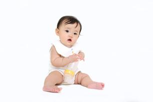 屋内白バックでお座りする新生児の赤ちゃん。新生児、赤ちゃん、育児、健康、愛、幸せイメージの写真素材 [FYI01227946]