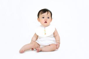 屋内白バックでお座りする新生児の赤ちゃん。新生児、赤ちゃん、育児、健康、愛、幸せイメージの写真素材 [FYI01227954]
