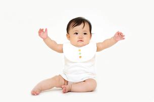 屋内白バックでお座りする新生児の赤ちゃん。新生児、赤ちゃん、育児、健康、愛、幸せイメージの写真素材 [FYI01227956]