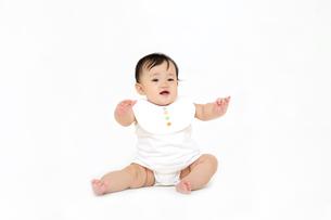 屋内白バックでお座りする新生児の赤ちゃん。新生児、赤ちゃん、育児、健康、愛、幸せイメージの写真素材 [FYI01227958]
