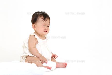 屋内白バックでお座りする新生児の赤ちゃん。新生児、赤ちゃん、育児、健康、愛、幸せイメージの写真素材 [FYI01227978]