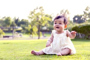 屋外の緑地でお座りする女の子の赤ちゃん。新生児、育児、健康、成長イメージの写真素材 [FYI01228002]