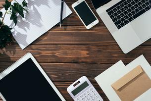 ノート、ペン、ノートパソコン、木目の背景。の写真素材 [FYI01228944]