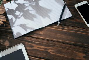 ノート、ペン、ノートパソコン、木目の背景。の写真素材 [FYI01228947]