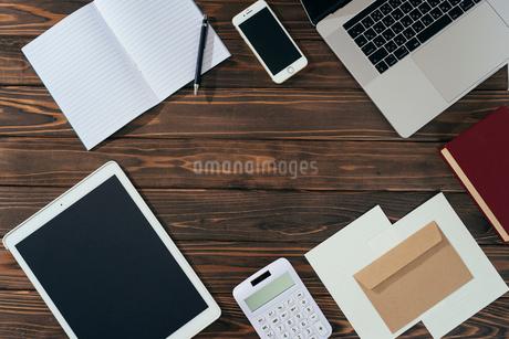 ノート、ペン、ノートパソコン、木目の背景。の写真素材 [FYI01228948]