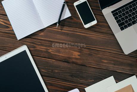 ノート、ペン、ノートパソコン、木目の背景。の写真素材 [FYI01228949]