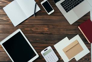 ノート、ペン、ノートパソコン、木目の背景。の写真素材 [FYI01228951]