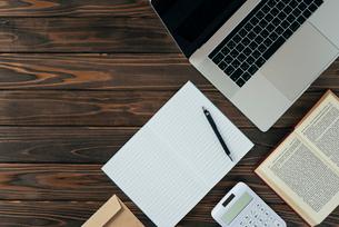 ノート、ペン、ノートパソコン、木目の背景。の写真素材 [FYI01228954]