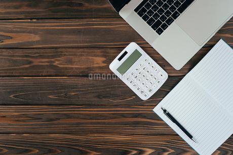 ノート、ペン、ノートパソコン、木目の背景。の写真素材 [FYI01228955]