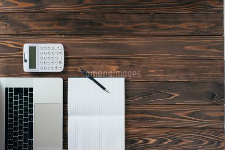 ノート、ペン、ノートパソコン、木目の背景。の写真素材 [FYI01228956]