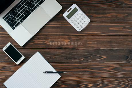 ノート、ペン、ノートパソコン、木目の背景。の写真素材 [FYI01228957]