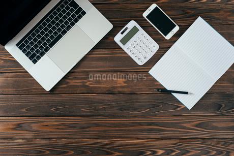 ノート、ペン、ノートパソコン、木目の背景。の写真素材 [FYI01228958]