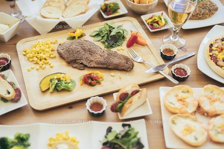パーティー料理。ステーキ・野菜・パン・グラス・グラタン等。の写真素材 [FYI01230234]