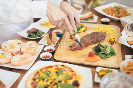 ナイフとフォークを持ってステーキを切る白シャツの男性の手と料理の写真素材 [FYI01230243]