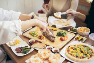 ナイフとフォークを持ってステーキを切る白シャツの男性の手と料理の写真素材 [FYI01230247]