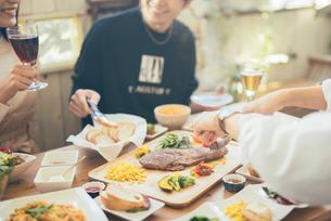 テラスでパーティ中に談笑している男女。ステーキを切っている手。の写真素材 [FYI01230249]
