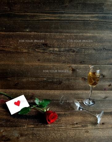 一輪の赤い薔薇とメッセージカードとシャンパングラスの写真素材 [FYI01231625]