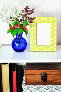 カラーボックスの上のフラワーアレンジメントとフォトフレームの写真素材 [FYI01231636]