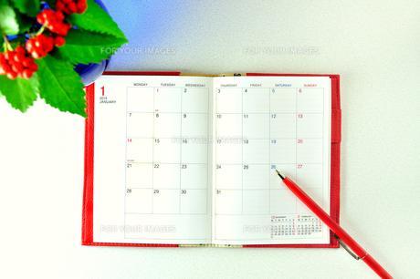見開きの赤い手帳と赤いペンの写真素材 [FYI01232005]
