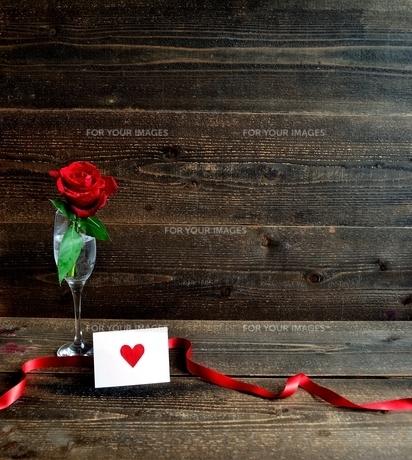 シャンパングラスにいけた一輪の赤い薔薇とメッセージカードの写真素材 [FYI01232020]