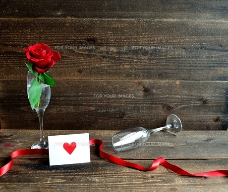 シャンパングラスにいけた一輪の赤い薔薇とメッセージカードの写真素材 [FYI01232021]