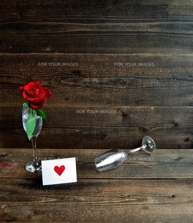 シャンパングラスにいけた一輪の赤い薔薇とメッセージカードの写真素材 [FYI01232022]
