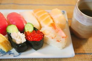 日本食のお寿司 白い皿に乗ったイクラ、生エビ、カニ、サーモン、ホタテ、イカとマグロの鮮魚の写真素材 [FYI01232334]