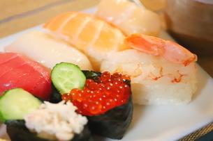 日本食のお寿司 白い皿に乗ったイクラ、生エビ、カニ、サーモン、ホタテ、イカとマグロの鮮魚の写真素材 [FYI01232337]