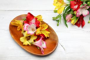 木製の皿に盛ったアルストロメリアとユリの写真素材 [FYI01232966]