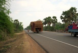 カンボジア国道6号線を走る過積載のバイクの写真素材 [FYI01233652]