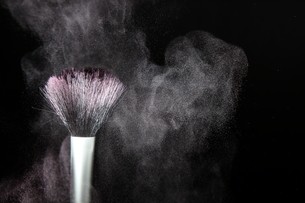 化粧筆と飛散るカラーパウダーの写真素材 [FYI01236006]