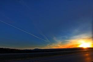 アメリカ横断 高速道路にて地平線 夕日をのぞむの写真素材 [FYI01237759]