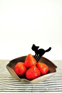 皿に盛ったイチゴと黒猫型のフォークの写真素材 [FYI01238407]