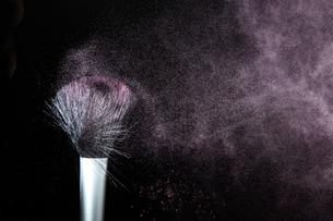化粧筆と飛散るカラーパウダーの写真素材 [FYI01238643]