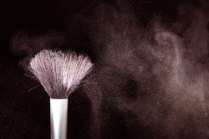 化粧筆と飛散るカラーパウダーの写真素材 [FYI01238644]