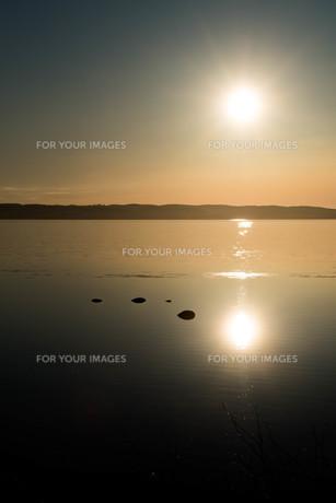 静かな湖面に映る夕日の写真素材 [FYI01239267]
