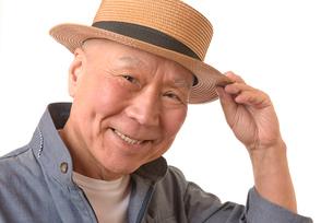 笑顔のシニアと麦わら帽子の写真素材 [FYI01240112]