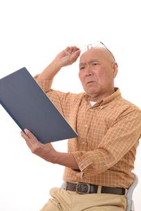 老眼で本を読む日本人シニアの写真素材 [FYI01240595]