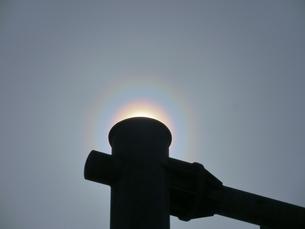 道路案内標識の支柱で太陽を隠した花粉光環の写真素材 [FYI01242390]