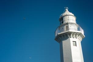 灯台の向こうの青空を飛行機と鳥が飛んでいるの写真素材 [FYI01242527]