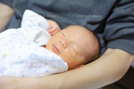 大人の腕の中で眠る赤ちゃんの素材の写真素材 [FYI01242785]