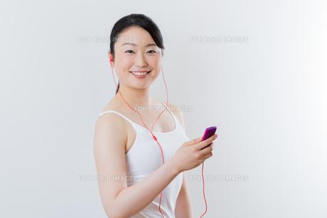 フィトネスしながら音楽を聴く 女性の写真素材 [FYI01242844]