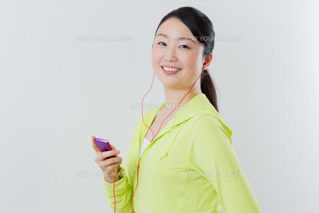 フィトネスしながら音楽を聴く 女性の写真素材 [FYI01242845]