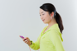 フィトネスしながら音楽を聴く 女性の写真素材 [FYI01242846]