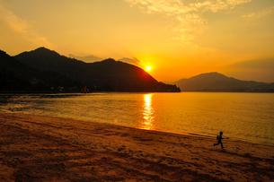 宮島の夕日と海岸を走る少年の写真素材 [FYI01243112]