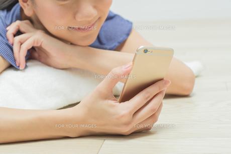 寝そべってスマホを触る女性の写真素材 [FYI01243401]