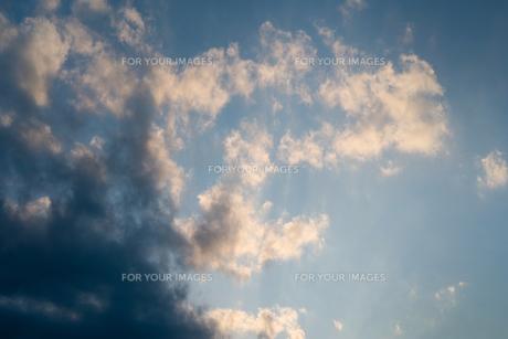 太陽が黒雲の隙間から光線となって雲を照らしているの写真素材 [FYI01243567]
