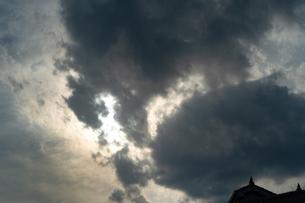 尖塔のような屋根の家の向こうの黒い雲の隙間から漏れる太陽の光と色の写真素材 [FYI01244207]